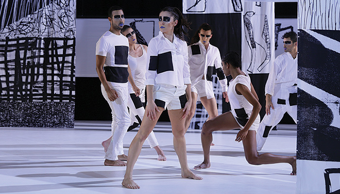 Dancers dressed in black and white stand on a black and white stage