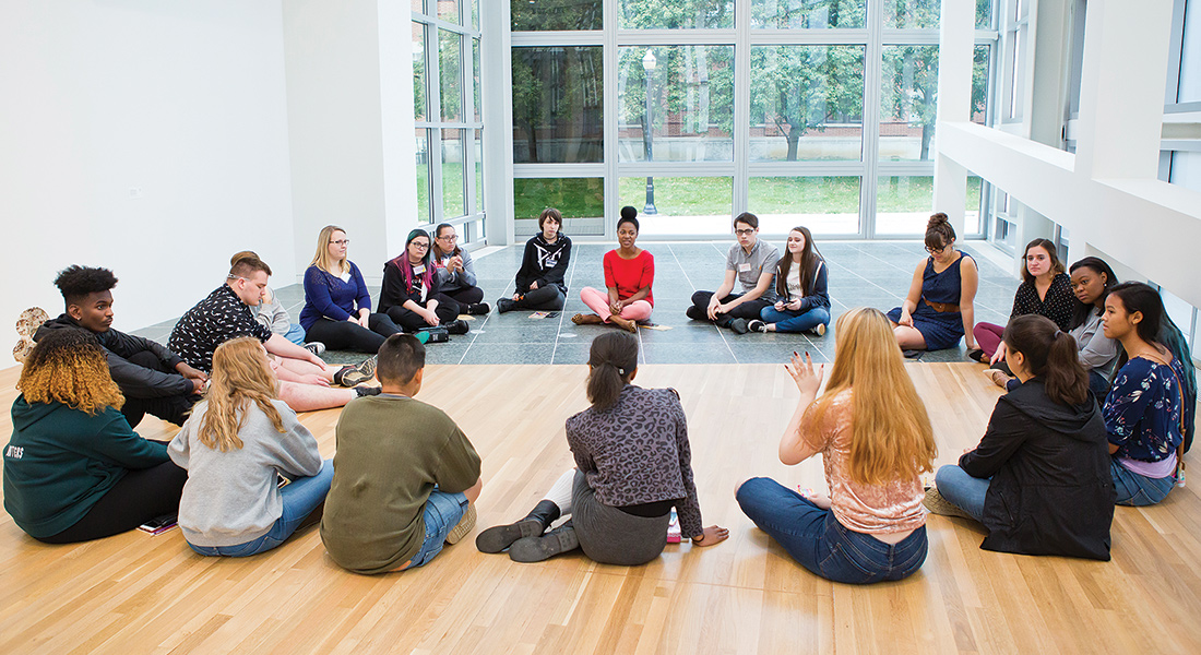 Students sit in a circle in the galleries