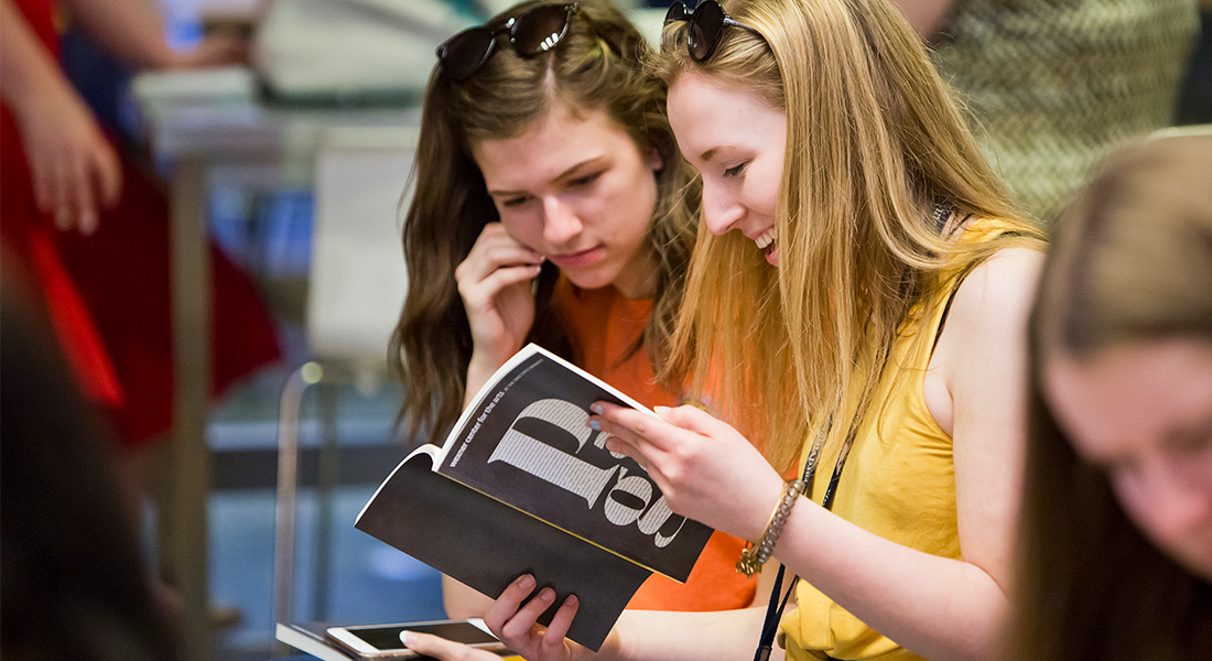 Two girls look at a Pages brochure