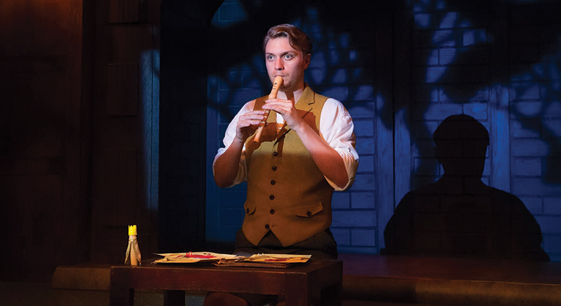 A man plays the recorder on stage