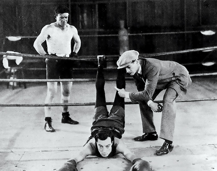 A man lays across the ropes in a boxing ring while two people watch