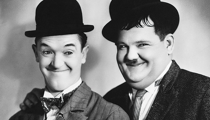 Two men in bowler hats smile for the camera