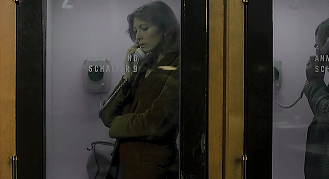 A woman on the phone in a phone booth