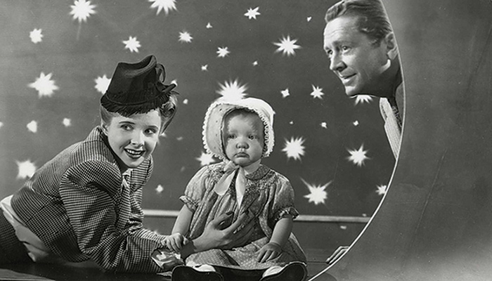 A family of three poses in a photo studio decorated with a moon and stars