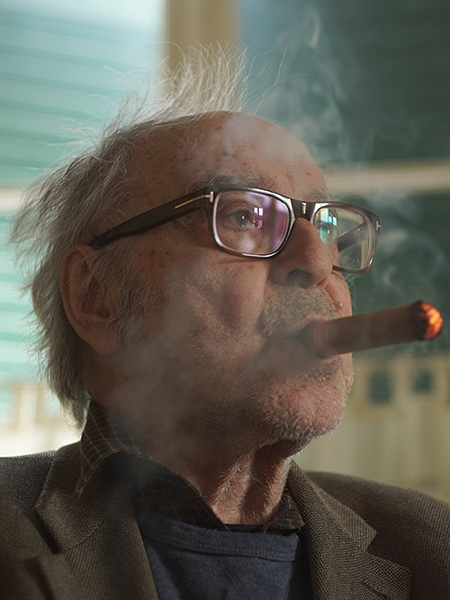 Older man in glasses smoking a cigar