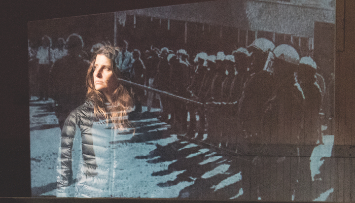 Actress Mia Barron stands behind a transparent screen with an image of police in riot gear during performance of Lars Jan & Early Morning Opera's production of Joan Didion's The White Album