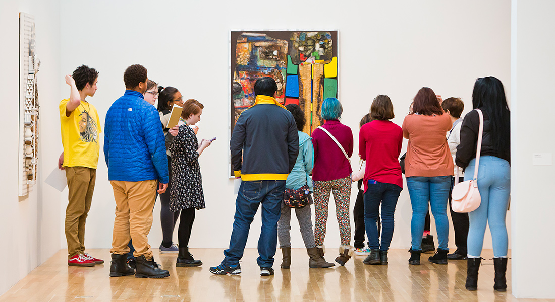 A group of people tour a gallery.