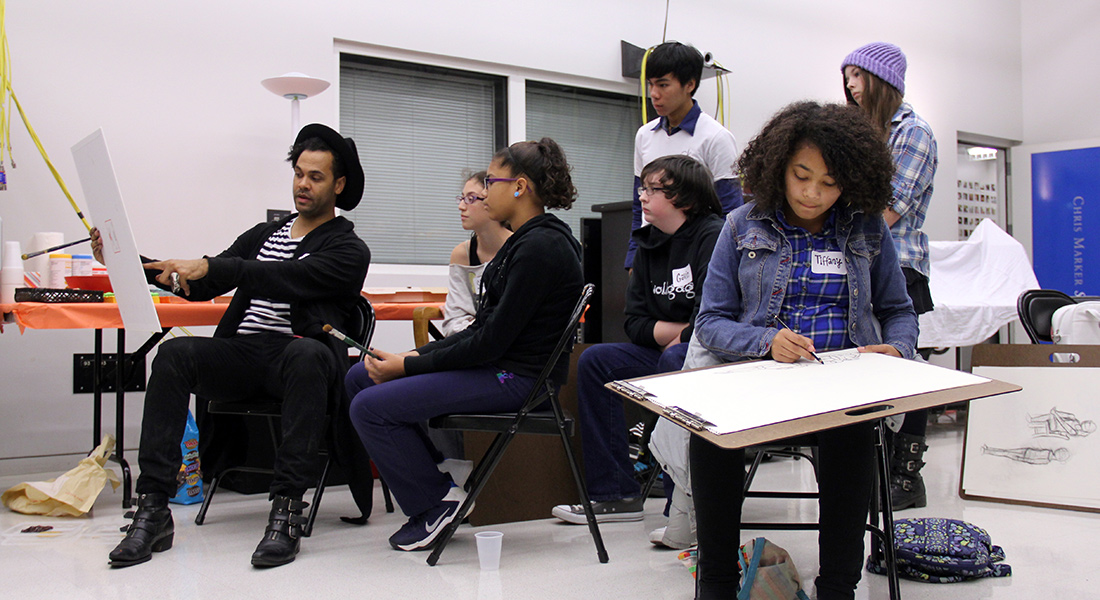 Teens get drawing instruction from an artist.