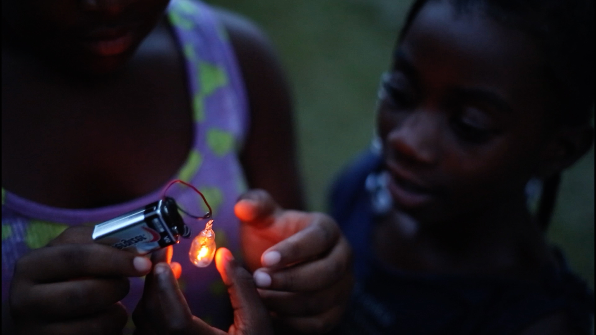 A still of two children powering a small light with a 9-volt battery from the 2018 documentary Hale County This Morning, This Evening by director RaMell Ross