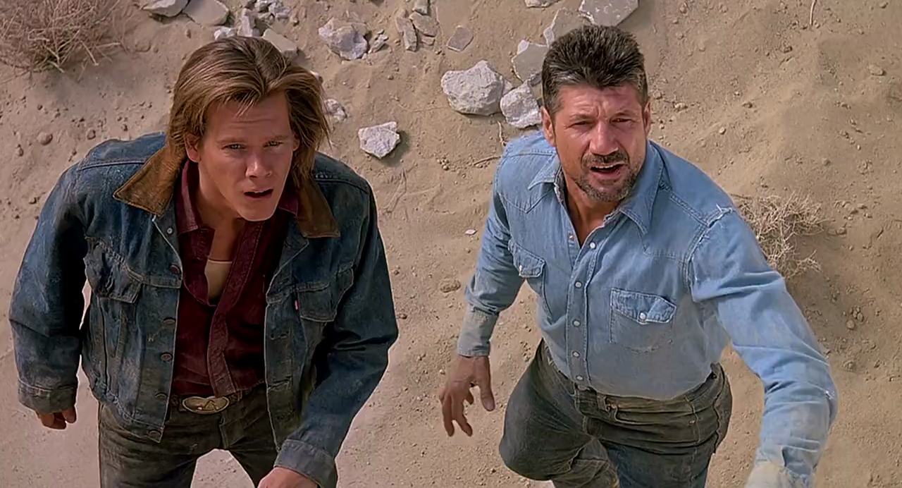 Actors Kevin Bacon and Fred Ward looking dazed in the desert in the 1990 scifi action film Tremors