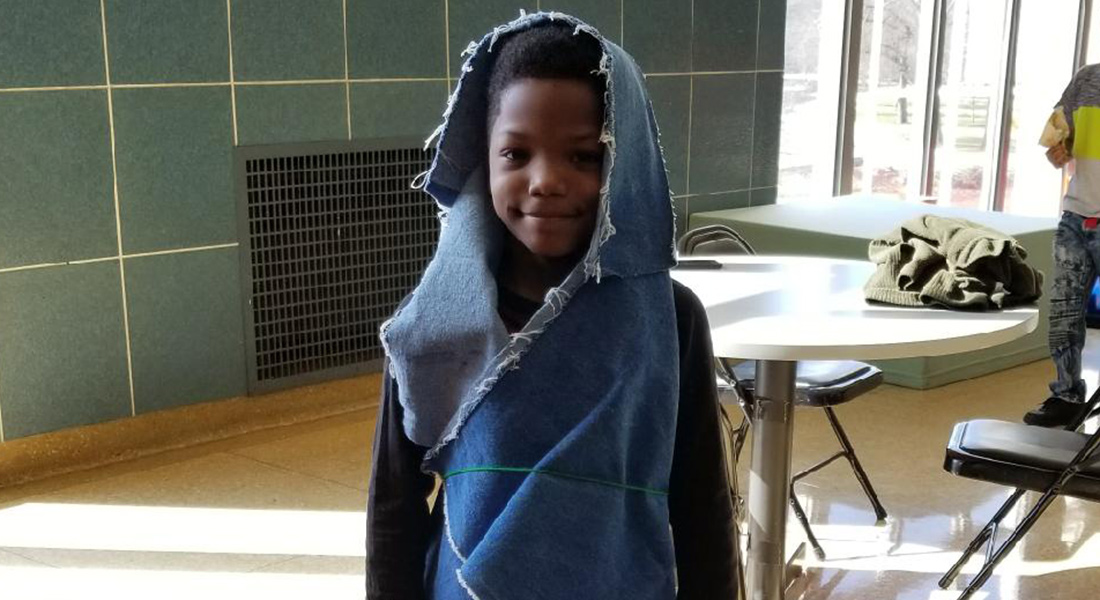 A child wraps himself in fabric.