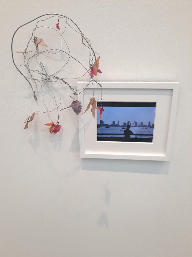Image of a Precario sculpture made by artist Cecilia Vicuña from found objects including a small frame with a picture inside. Work is on view at the Wexner Center for the Arts in the exhibition Cecilia Vicuña: Lo Precario/The Precarious