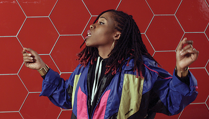 A young woman of color in bright robes sings against a red tile backdrop in the video work RISE by Barbara Wagner and Benjamin de Burca