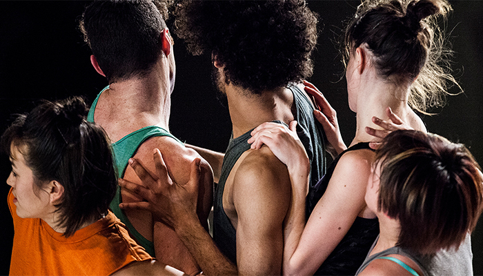 A group of five dancers stand closely together, their backs to the camera, in a promotional still for choreographer Faye Driscoll's Thank You for Coming: Attendance