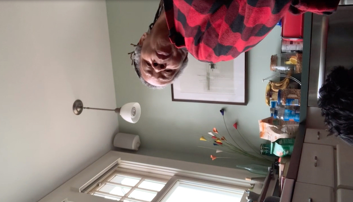 Dancer and choreographer Bebe Miller performs a movement work in her home, captured on a phone attached to her foot, which turns the view of the room sideways