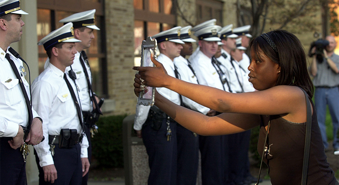 A black women holds a photo out to a line of police officers.