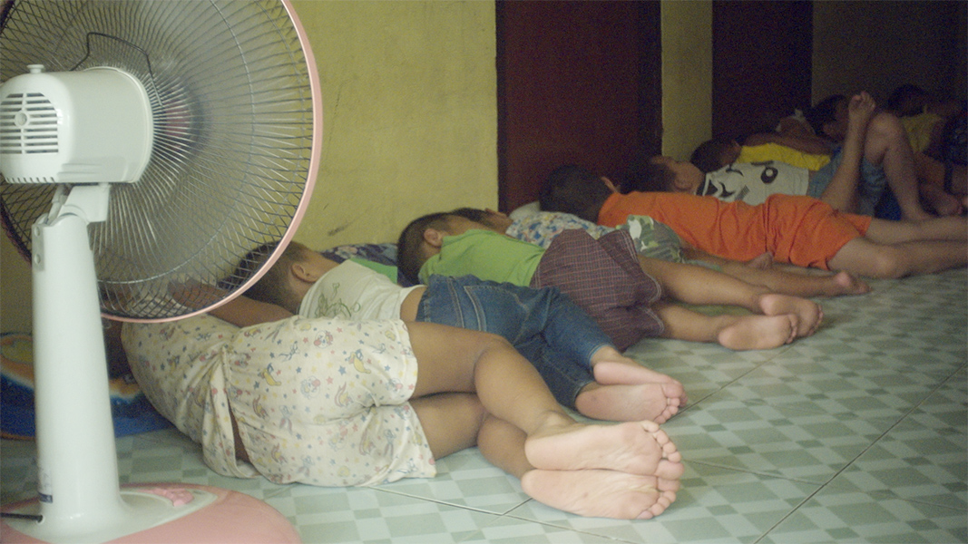 A row of children lay napping on a tile floor with an electric fan pointed at them.