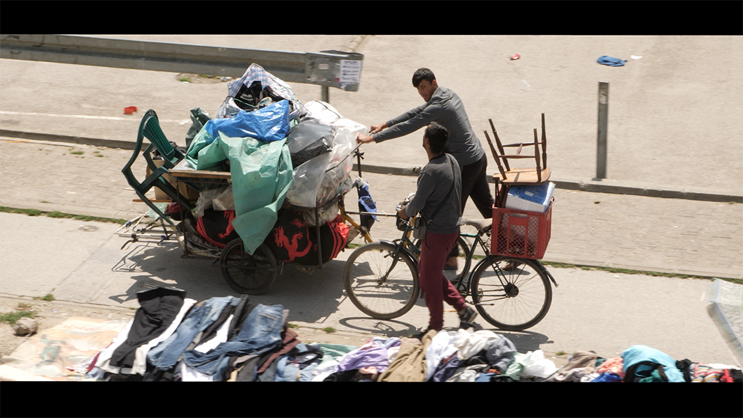 Two men on bikes push a cart laden with tarps, blankets, chairs, and other objects.