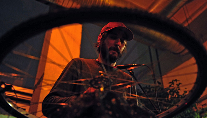 Rob Frye in hat performing, viewed through a spoked bicycle wheel