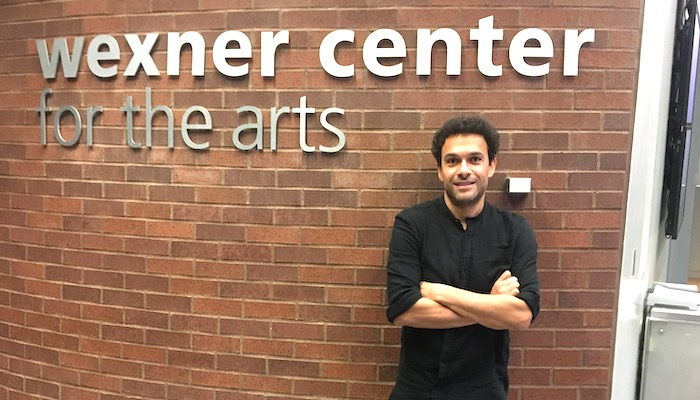 Filmmaker Tamer El Said stands against a brick wall with the Wexner Center for the Arts logo in brushed metal lettering above him
