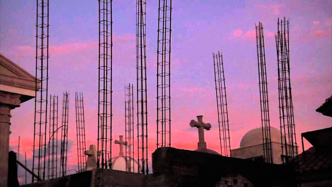 A rooftop scene of crosses and rebar towers against a purple and pink sunset