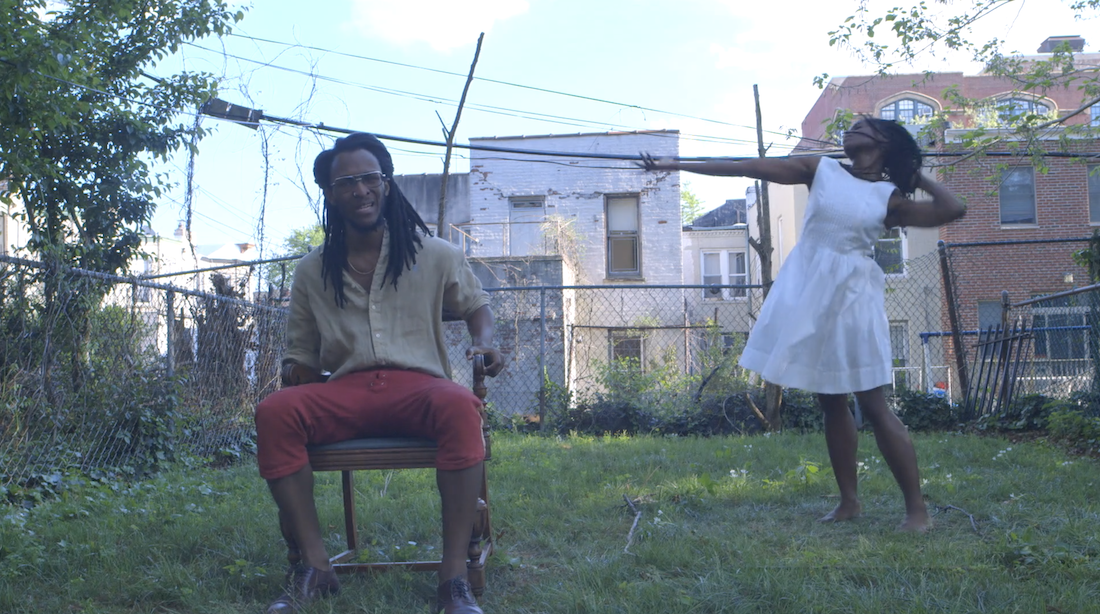On the left, in an outdoor, grassy setting with buildings in the background, a Black man with long braids sits in a chair singing as a Black woman with long braids in a white dress dances on the right side