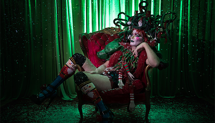 Taylor Mac sits in a red plush chair while wearing festive attire and a snake headdress.