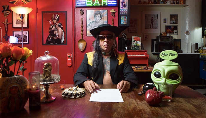 Gómez-Peña is seated in his home studio. He is wearing a black jacket with no shirt underneath. He wears a hat and in front of him is a piece of paper. To his right is a plastic, green alien head and to his left is an ashtray with a cigarette resting in it.
